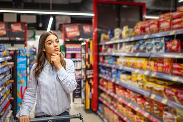 Young woman looking confused choosing products from an aisle at the supermarket walking with her trolley rubbing her chin thoughtfully copyspace people lifestyle consumerism retail buying customer