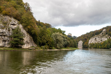 Nature reserve at Danube river breakthrough near Kelheim, Bavaria, Germany in autumn with limestone rock formations and Befreiungshalle on the Michelsberg in the background