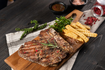 The steak of beef grilled served with french frie placed on chop real wood, no dish and decorate with many herb as pepper and rosemary. All placed on the grey dish towel and wood background. Flat lay