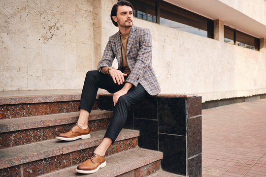 Young handsome stylish man in checkered jacket thoughtfully looking away while sitting outdoor