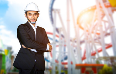 Engineer or Businessman standing on the blurred image of roller coaster in attraction park.