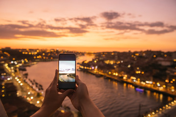 woman, hands holding smartphone with a photo of panoramic view of Porto at sunset, Portugal