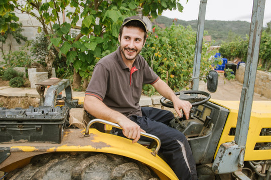Portrait of a smiling farm tractor driver in a vineyard