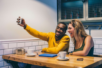 Portrait of laughing couple taking selfie with smartphone in a coffee shop