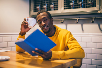 Portrait of man in a coffee shop reading a book