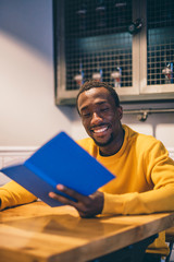 Portrait of smiling man in a coffee shop reading a book