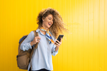 Laughing young woman with backpack in front of yellow background looking at cell phone