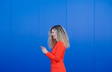 Profile of young woman wearing red dress in front of blue background looking at cell phone