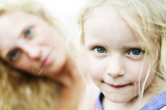 Germany, North Rhine Westphalia, Cologne, Portrait of girl biting lips while her mother in, close up