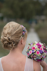 Germany, blond bride with updo and bridal bouquet, back view