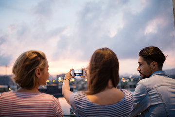 Spain, Barcelona, back view of three friends taking a picture of view with smartphone