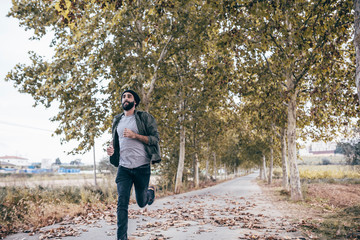 Spain, Tarragona, young man running on autumnal country road