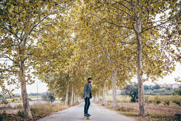 Spain, Tarragona, young man with longboard on autumnal country road