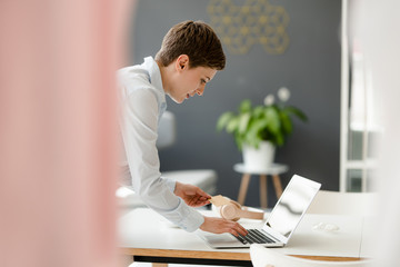 Businesswoman using laptop and credit card on table in office