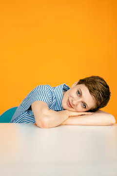 Portrait of woman resting on table with orange background