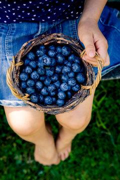 Little girl with wicker basket of blueberries
