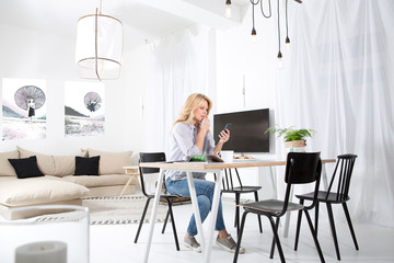 Woman sitting at the table in her living room looking at smartphone