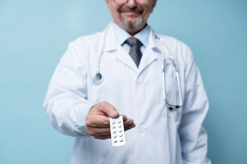 Portrait of a mature doctor standing in a hospital and holding medicine in hand - Stock Photo