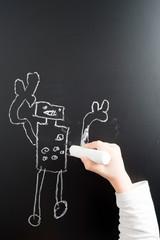 Little boy's hand drawing robot on a blackboard