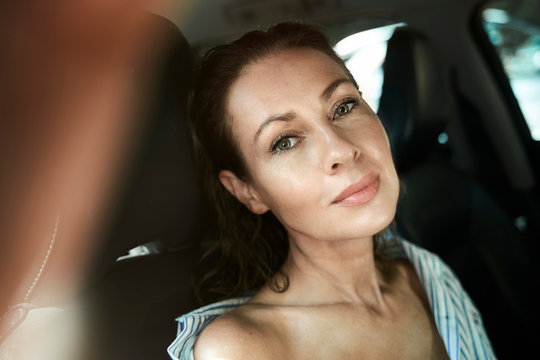 Portrait of a beautiful mature woman in a car