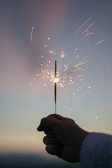 Hand holding a burning sparkler
