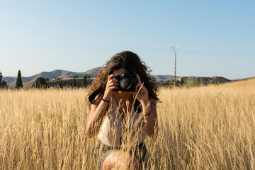Young woman taking a picture with a camera in a meadow at sun