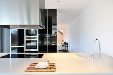 Modern kitchen with extractor hood and iron faucet