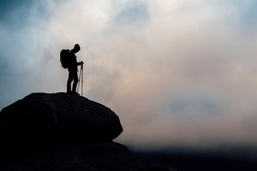 Silhouette of mountain hiker with backpack and walking stick on clouds