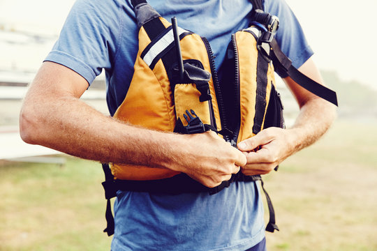 Man zips up his life jacket in preparation for kayaking in Casco Bay