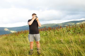 Man in black t-shirt takes pictures of Carpathians landscapes