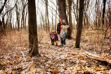 Father walks in woods with children holding baby and daughters hand