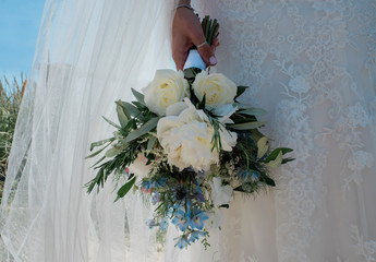 Bride standing in her lace wedding dress holding her bouquet of flowers
