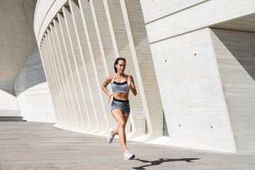 Full body of female athlete in sportswear running on concrete