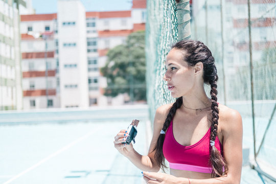 Colorful image of female athlete eating a recovery bar on court