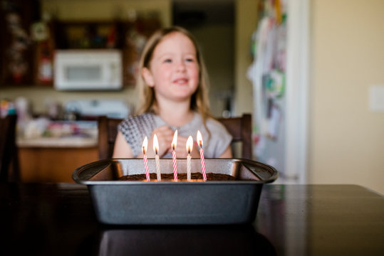 Candles on birthday cake 5 year old girl smiling in background