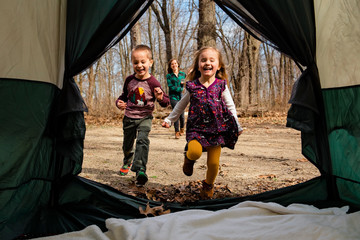 Brother and sister run laughing into tent with mother behind them