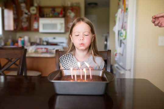 5 year old girl blows out candles on birthday cake at home in kitchen