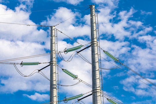 A closeup view on the top half of a double poled electric pylon supporting medium voltage cables with green insulators, city and town infrastructure.