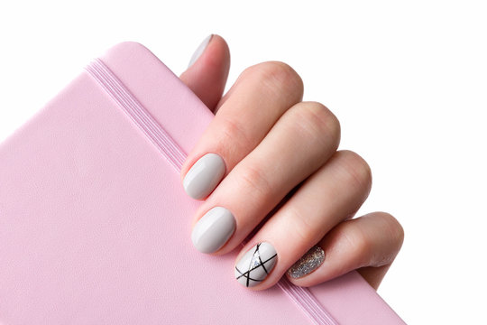 Females hand with modern manicure holds pink notepad close up