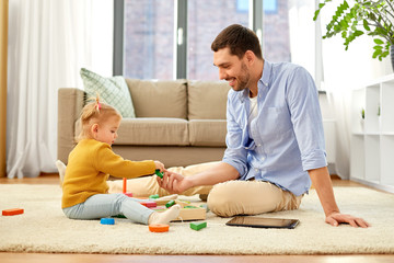 family, fatherhood and people concept - happy father and little baby daughter playing with wooden toy toy blocks kit at home