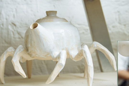 Original handmade ceramic teapot on the shelf of the Potter's workshop. White kettle in the style of a spider. Strange dishes on the legs