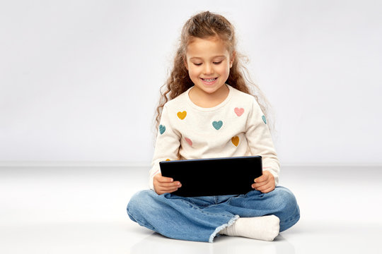 childhood and people concept - beautiful smiling girl with tablet computer sitting on floor over grey background