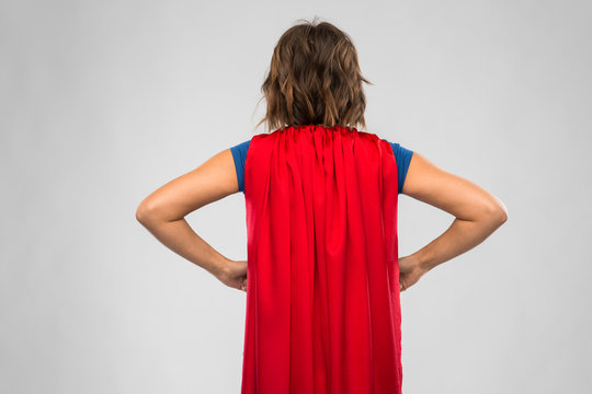 women's power and people concept - back view of young woman in red superhero cape over grey background