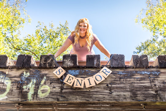 Teen girl poses for a high school senior portrait photo outdoors on a bridge with a sign saying Senior