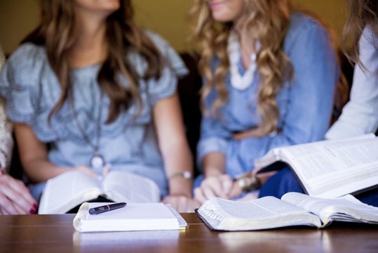 Closeup shot of females sitting and reading the bible while taking notes with a blurred background