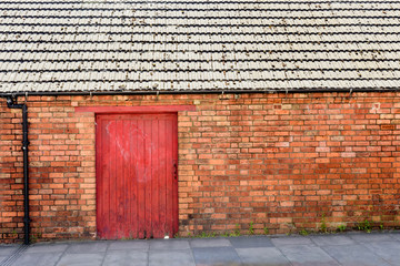 old wooden door gate in red brick wall in england town