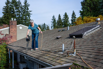 Rooftop view of suburban home, mature woman with leaf blower cleaning roof and gutter