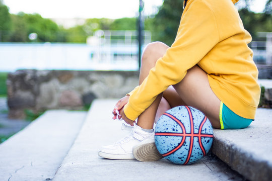 An unrecognizable woman basketball player sitting outdoors on the street