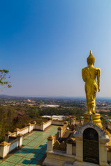 Fototapete - Golden buddha statue stand on mountain temple look to city