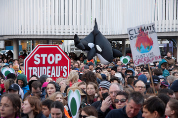 An inflatable orca is pictured next to a stop sign protesting the Canadian federal government's purchase of an oil pipeline project, during a climate strike rally in Vancouver